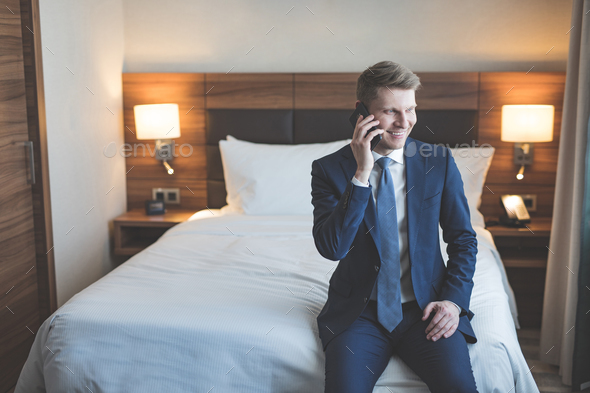Smiling man talking on a phone in the hotel - Stock Photo - Images