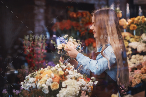 Smiling young girl with flowers - Stock Photo - Images
