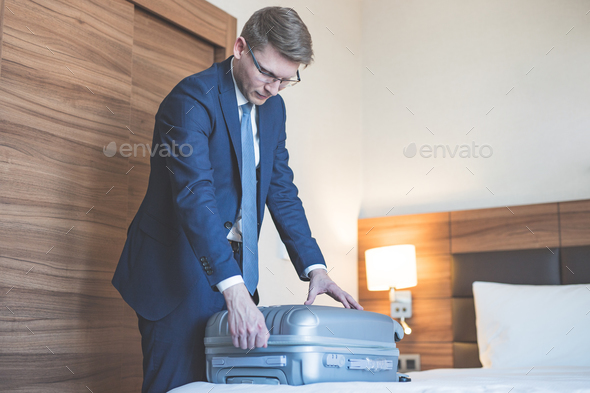 Young businessman with a suitcase indoors - Stock Photo - Images