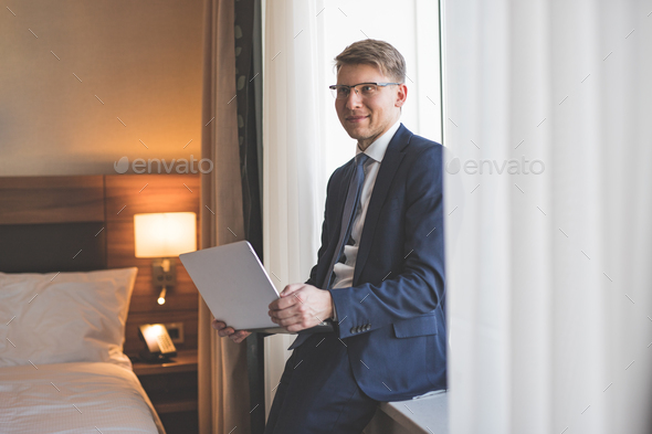 Smiling businessman with laptop - Stock Photo - Images