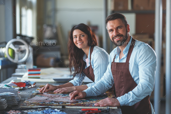 Smiling people with a mosaic in workshop - Stock Photo - Images