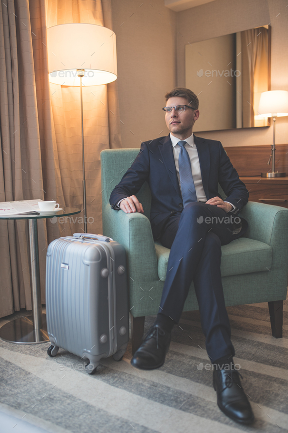 Young businessman with suitcase indoors - Stock Photo - Images