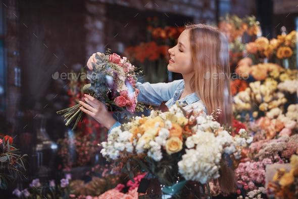 Smiling young girl in flower shop - Stock Photo - Images