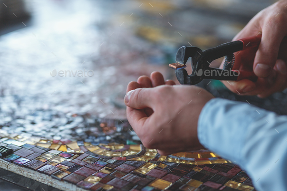 Men's hands cutting mosaic - Stock Photo - Images