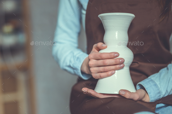 Master in apron holding a vase - Stock Photo - Images