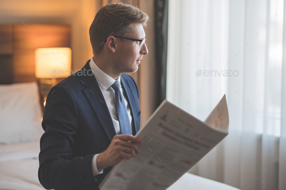 Young businessman with a newspaper - Stock Photo - Images