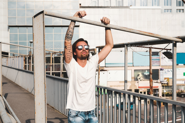 Attractive man with sunglasses hanging out in the city - Stock Photo - Images