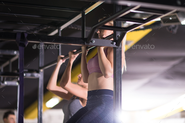 young athletes doing pull ups on the horizontal bar - Stock Photo - Images