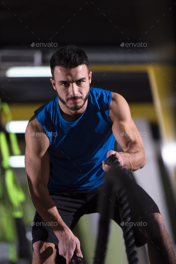 athlete man doing battle ropes cross fitness exercise - Stock Photo - Images