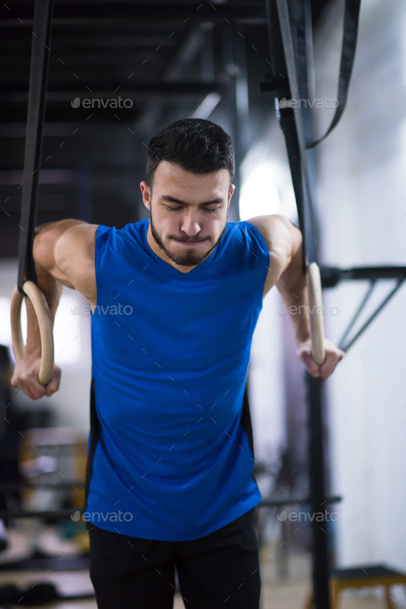 man working out pull ups with gymnastic rings - Stock Photo - Images