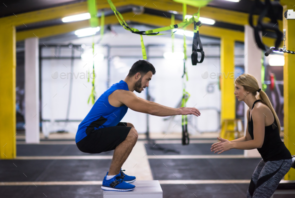 woman working out with personal trainer jumping on fit box - Stock Photo - Images