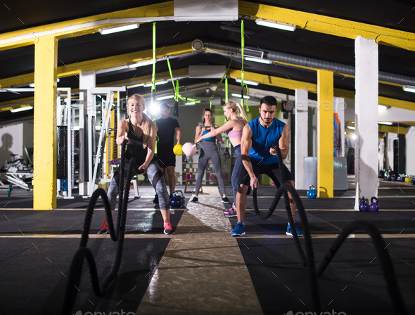 sports couple doing battle ropes cross fitness exercise - Stock Photo - Images
