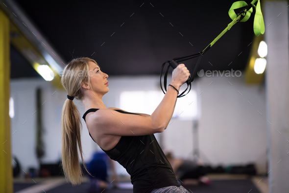 woman working out pull ups with gymnastic rings - Stock Photo - Images