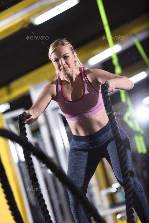 athlete woman doing battle ropes cross fitness exercise - Stock Photo - Images