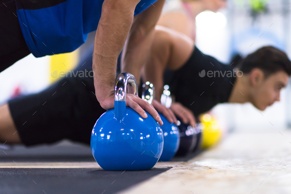 young athletes doing pushups with kettlebells - Stock Photo - Images