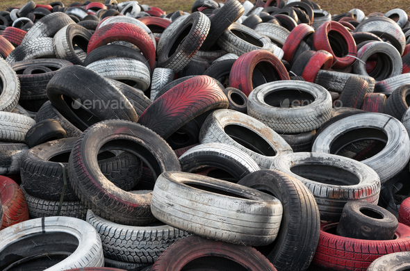 Variety of red white and black waste car tires piled in a big pile - Stock Photo - Images