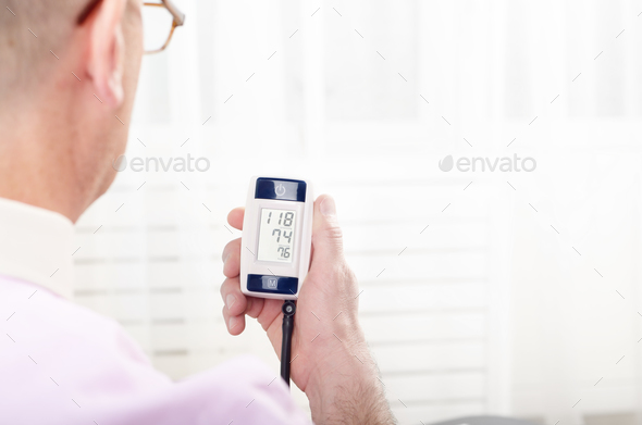 Man read measurement results from personal digital blood pressur - Stock Photo - Images