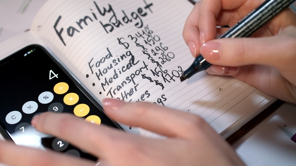 woman calculate family budget on calculator and writing in notebook