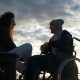 Happy Couple - Disabled Young Man in a Wheelchair with Young Woman Enjoying the Sunset Together - VideoHive Item for Sale