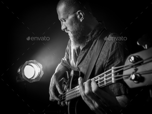 Bearded man playing bass guitar on stage - Stock Photo - Images