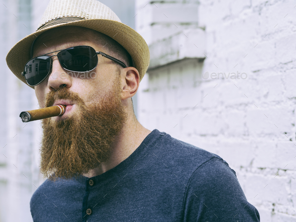 Bearded man with sunglasses smoking a cigar - Stock Photo - Images
