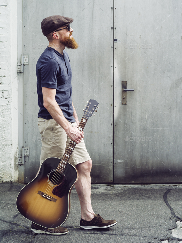Bearded man walking with acoustic guitar - Stock Photo - Images