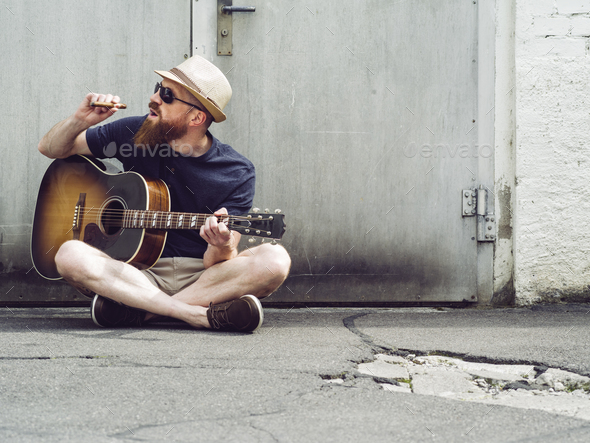 Bearded man playing acoustic guitar and smoking cigar - Stock Photo - Images