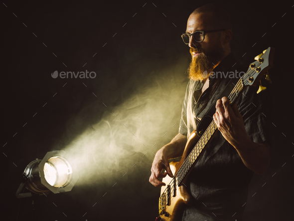 Bearded man playing bass guitar with spotlight - Stock Photo - Images