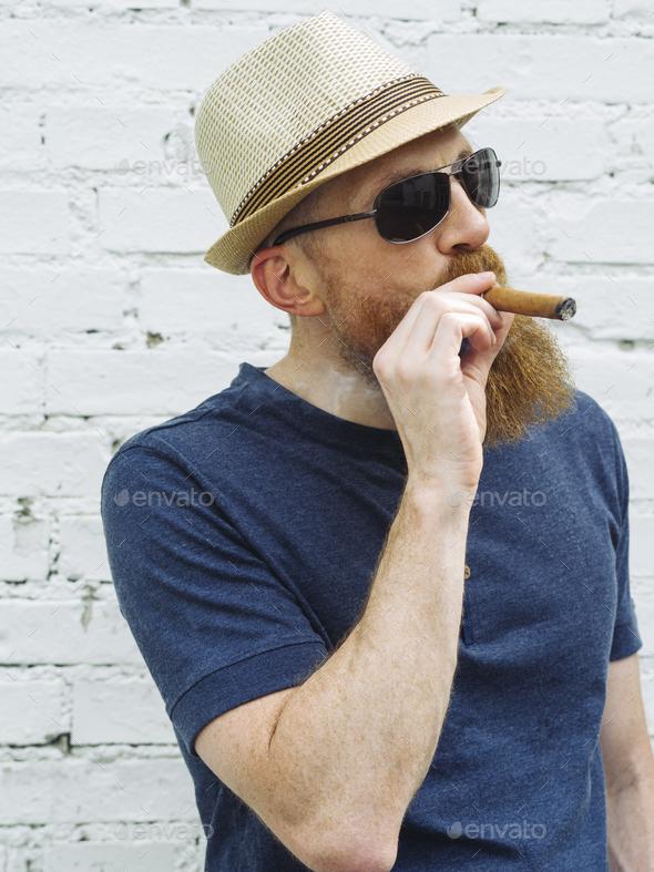 Bearded man smoking a cigar - Stock Photo - Images