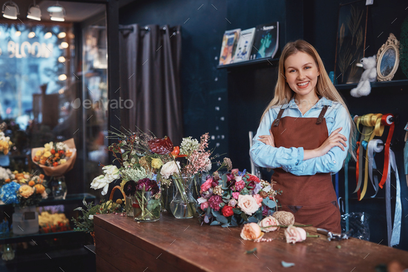 Smiling young florist in an apron - Stock Photo - Images