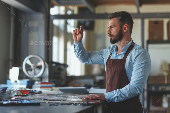 Young master with a mosaic in workshop - Stock Photo - Images