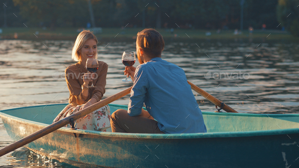 Attractive couple with glasses in a boat - Stock Photo - Images