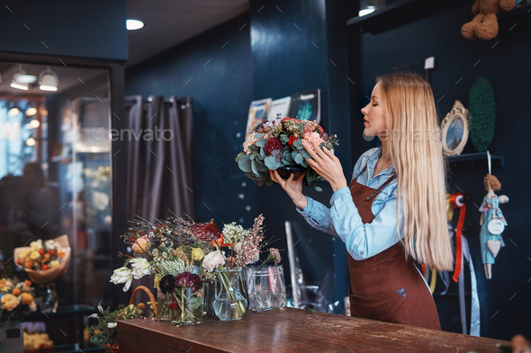 Young florist with bouquet of flowers - Stock Photo - Images