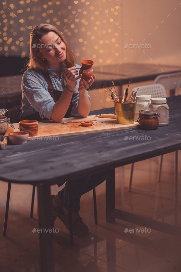 Smiling woman in a pottery studio - Stock Photo - Images