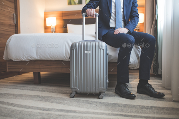Young businessman with a suitcase in room - Stock Photo - Images