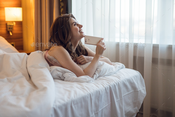 Dreaming young girl with a phone in room - Stock Photo - Images