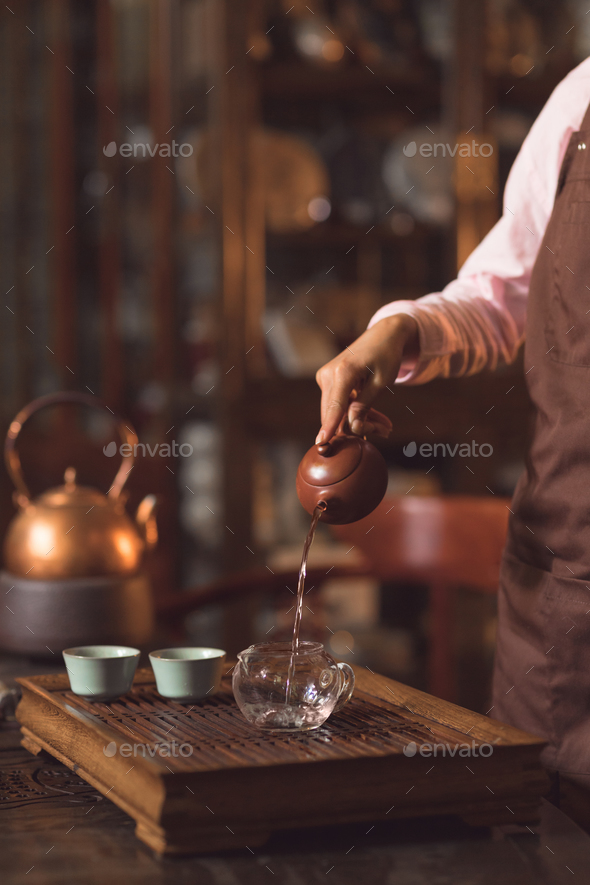 Tea master pouring tea indoors - Stock Photo - Images