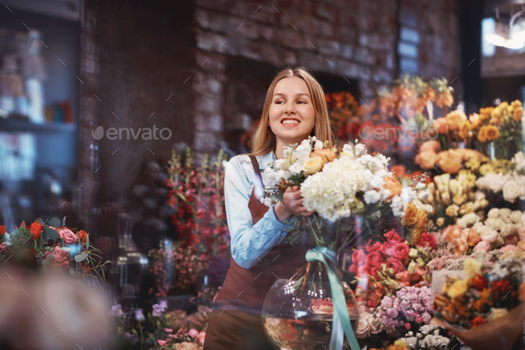 Smiling young florist in the store - Stock Photo - Images