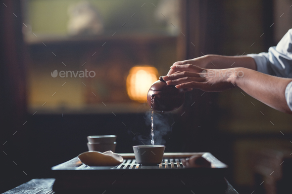 Female hands pouring tea from teapot - Stock Photo - Images