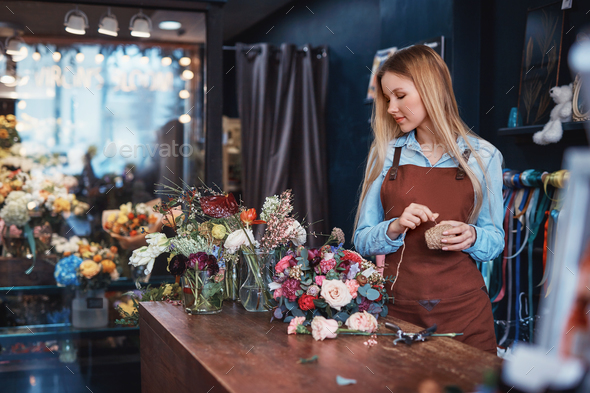 Young florist in an apron - Stock Photo - Images