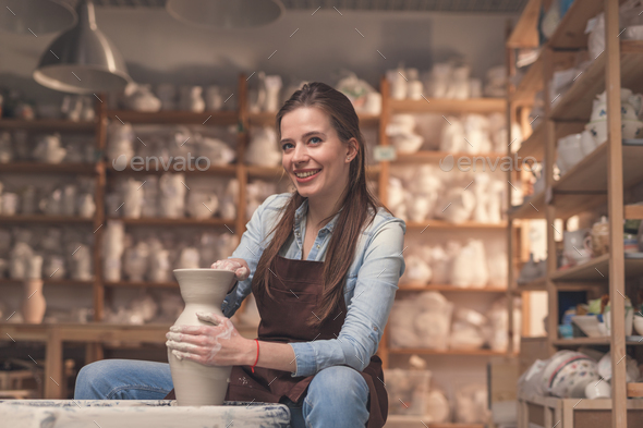 Smiling girl working on a potter's wheel - Stock Photo - Images