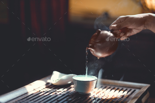 Tea master pouring tea in sunlight - Stock Photo - Images