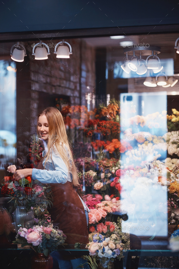 Young florist with bouquet indoors - Stock Photo - Images