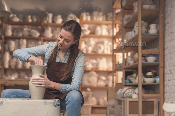 Young girl working on a potter's wheel - Stock Photo - Images