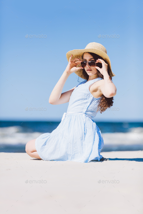 A girl in straw hat sitting on a beach by the sea - Stock Photo - Images