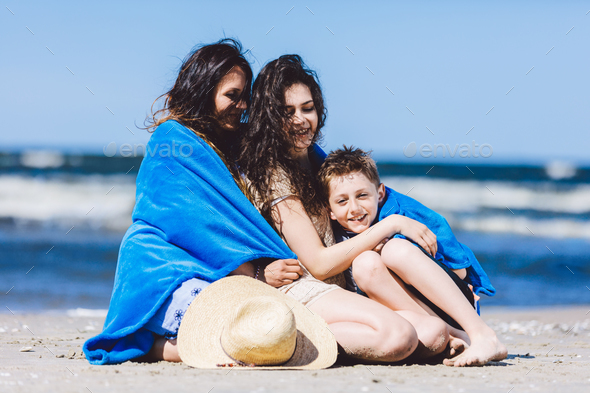 Mother and her children wrapped in a blanket by the sea. - Stock Photo - Images