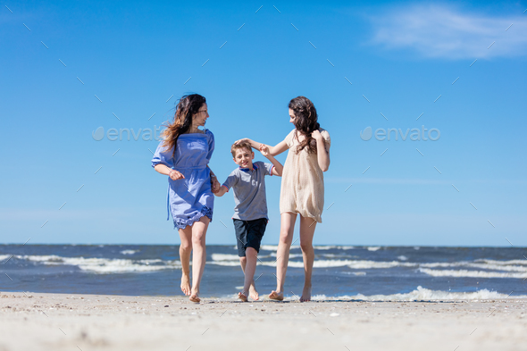Mother and her children having a walk by the sea. - Stock Photo - Images