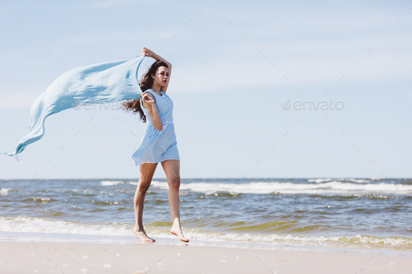 Pretty girl walking by the sea with a blue waving scarf. - Stock Photo - Images
