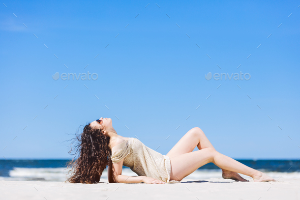 Young woman laying on the beach, sunbathing. - Stock Photo - Images