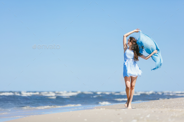 Young girl walking on the beach with blue scarf - Stock Photo - Images